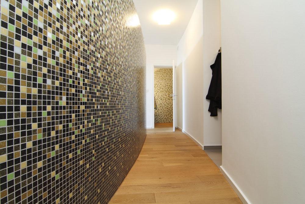 Fitnes miestnosť od priestoru sauny ahygienického zázemia oddeľuje výrazná stena obložená mozaikou.