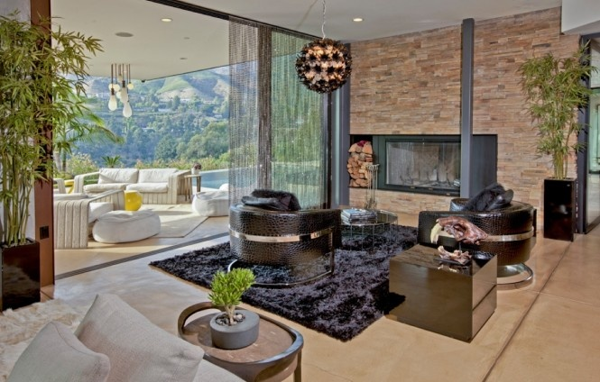 Závideniahodný pohľad na tento priestor vytvárajú nástenné obklady doplnené prírodným drevom a vystavené dekorácie z kameňa, ktoré kontrastujú s ultra elegantným osvietením a lesklým nábytkom.