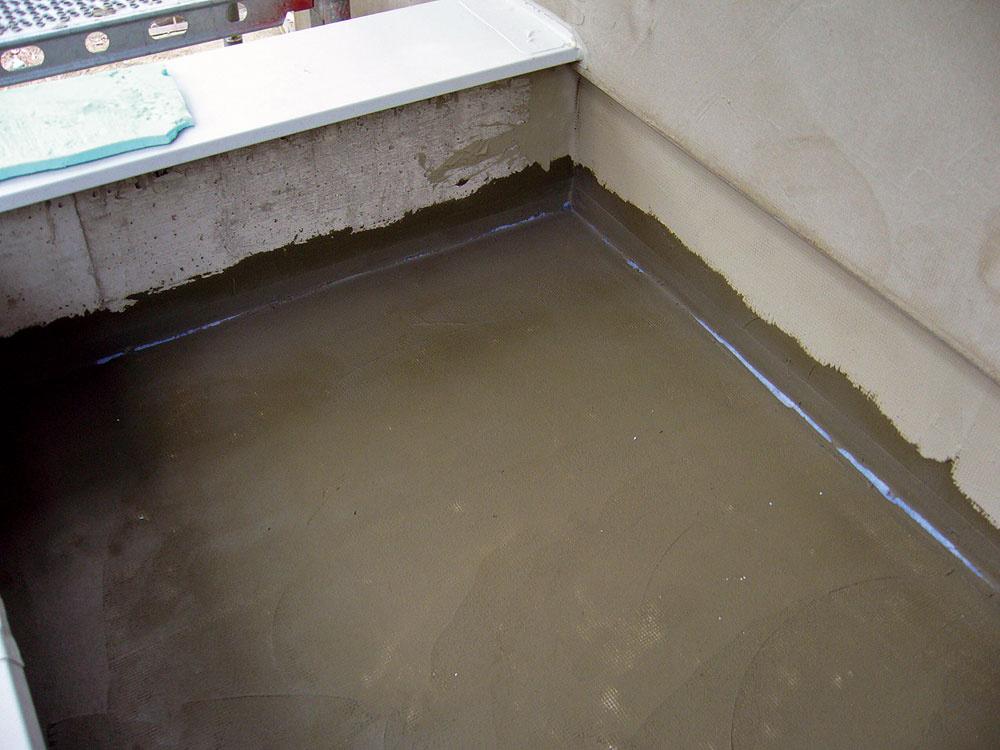 Detaily, ako napríklad priestupy či miesta styku podlahy so stenou, sa prekryjú špeciálnou gumenou páskou azapracujú sa do prvej vrstvy stierky. Vždy je nevyhnutné použiť dvojzložkovú hydroizolačnú stierku. Tekutá zložka zabezpečuje kvalitu hydroizolačnej stierky najmä zhľadiska pružnosti aprídržnosti.