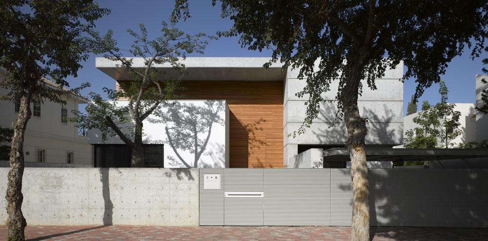 """Dva bloky ahlboké zastrešenie vytvárajú na priečelí domu od ateliéru Pitsou Kedem Architect monumentálnu """"bránu"""". Vedľa tohto exponovaného miesta sa vyníma americký tropický strom vlnovec (Ceiba insignis), ktorý sa vyskytuje aj vAmazónii. VIzraeli, kde sa mu darí aje pomerne populárny, kvitne vapríli. Jednou zjeho zvláštností je, že mladé konáre akmeň majú ostne."""