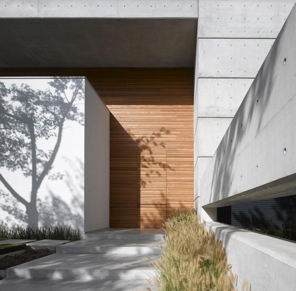 Na drevenej ploche zúzkych dosák takmer zanikajú vstupné dvere. Cestou po miernych schodoch zlešteného betónu upúta úzky priezor, cez ktorý vidieť trávnik pred salónom. Spomenieme si naň vobývacom priestore, kde je podobné úzke, dlhé anízke okno. Vľavo popri chodníku zbetónových kociek, ktorým sa dá vojsť do pracovne, vysadili pri múre juhoafrickú Sansevieriu cylindricu.