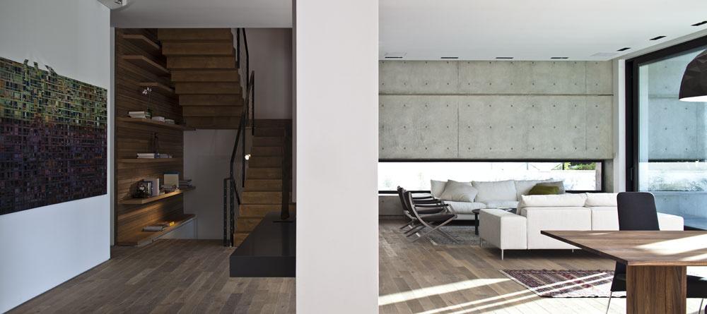 Stred prízemia zaberá priestor, ktorý vyúsťuje na schodište asvojím členením pripomína loď vo svätyni. Stenu vedľa schodišťa zdobí obraz od Dannyho Tabaka. Typické modernistické zábradlie zjednoduchého štvorcového oceľového profilu sbariérou zlaniek, natreté načierno, nájdeme aj oposchodie vyššie na balkóne obrátenom do záhrady. Pohovka akreslá (Paul/Poltroncina) vobývacej časti sú od talianskeho architekta adizajnéra Antonia Citteria.