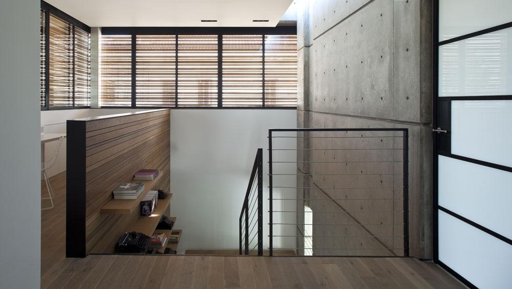 Drevená plocha členiaca fasádu prepúšťa svetlo do odpočinkového priestoru pri vyústení schodov aaj do predsiene na prízemí. Snímka zobrazuje aj ďalší zdroj svetla na schodisku – úzke okno, ktoré vedie do kúta obývacieho priestoru. Zasklený otvor je tiež pod stropom vedľa betónového múru. Dverami smliečnym sklom sa vchádza do veľkej spálne.