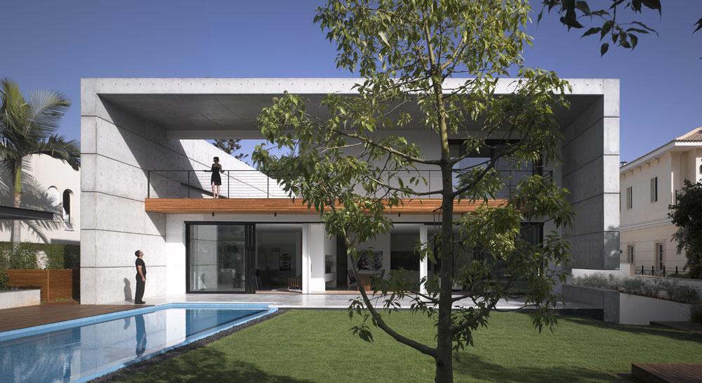 Pred západným slnkom je dom chránený mohutným prvkom pripomínajúcim bránu. Na hlbokom múre podopierajúcom zastrešenie sa ráno cez priechod zbalkóna na terasu zjaví pás slnečného svetla, ktorý stúpa po múre, zužuje sa apopoludní osvetľuje čoraz širší úsek betónovej zvislice. Múr terasy prerušuje vspodnej časti výklenok, ktorý je vnoci efektne osvetlený. Ešte viac tak vyniká schéma dvoch lomených plôch, ktorá sa vinej podobe objavuje na uličnom priečelí.