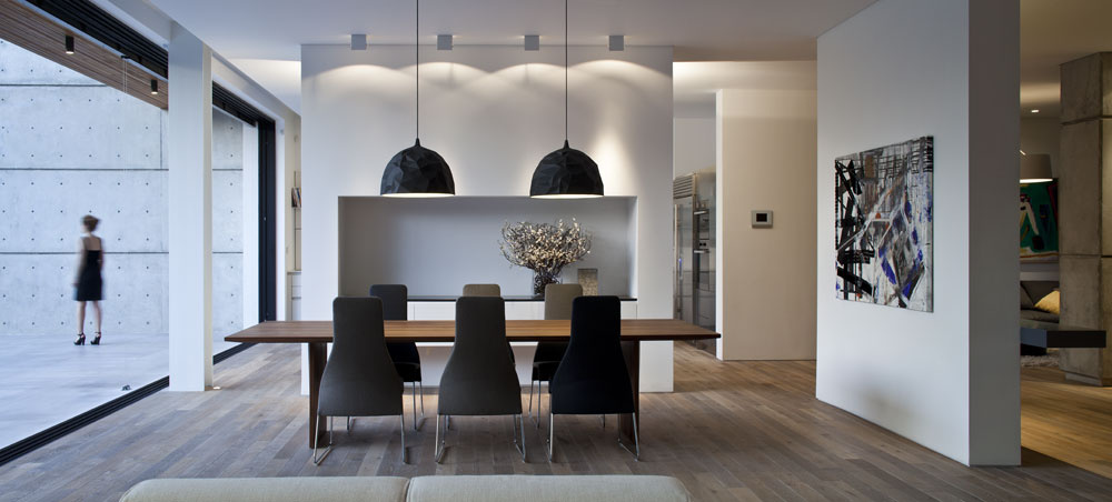 Atmosféra domu vzniká vďaka kontrastu nielen materiálov, ale aj miest ponorených vprítmí apartií vplnom svetle. Výrazne ktomu prispieva pomerne hlboký prienik obvodových múrov pod strop, ktorý dobre vidieť vľavej časti snímky. Vonkajší betónový múr svodorovným členením aotvormi po debnení nevniká do interiéru len vobývacom priestore. Na pravom okraji fotografie je ďalší príklad takéhoto prieniku – krátky úsek betónového múru oddeľuje vstupný priestor od salónu. Vjedálni visí maľba Anata Arona, azda najznámejšieho zautorov zobrazených diel.