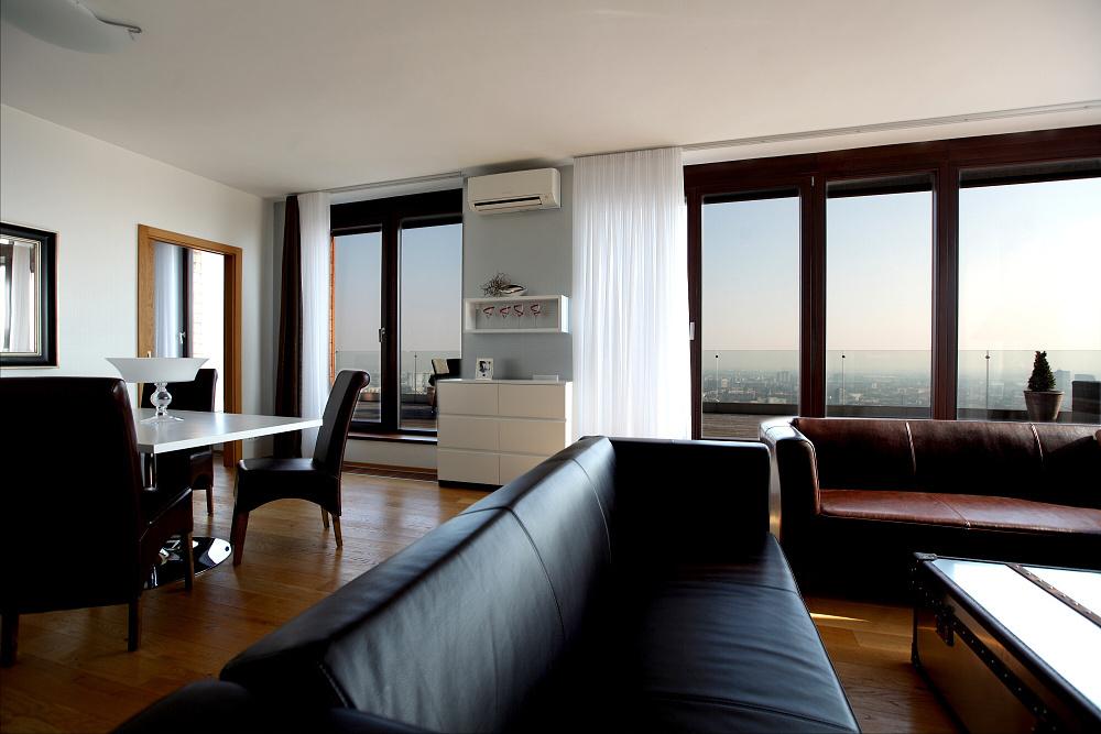 Nádherný pohľad na mesto cez terasu nie je narušený žiadnymi zbytočnosťami.... Na drevenej podlahe sa vyníma netradičný hliníkový stôl kombinovaný s kožou , ktorá je dominantná aj na sedačke a stoličkách v jedálenskej časti. Táto farebnosť sa  prirodzene spája s farbou dreva na terase. Všetko ostatné je čisté  a minimalistické. Teplo interiéru sa docielilo doplnkami teplých farieb.