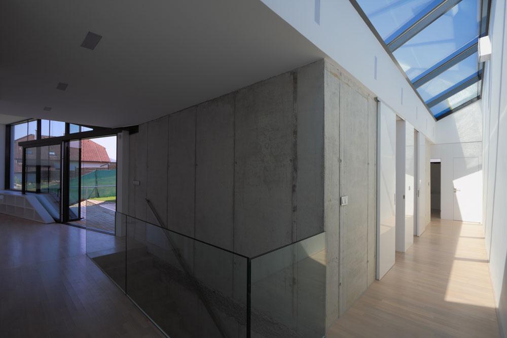 Zobývacej haly sa popri zasklenej fasáde otočenej kterase ado záhrady prechádza do nočnej časti domu so spálňou, hygienickým zázemím ašatníkom. Zasklená fasáda sa viaže ku všetkým obytným častiam domu aje dôležitým architektonickým prvkom jeho západnej strany. Nadrozmerné posuvné dvere zasklenej fasády sú umiestnené pod šikmým stropom, pričom konzola hornej vodiacej koľajnice je upevnená na špeciálne vyhotovenom oceľovom nosníku. Surový betón na vnútornej nosnej stene vytvára kontrast sdokonale hladkým povrchom bielej gletovanej omietky.