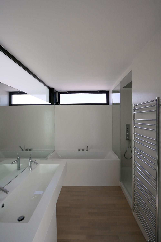 Vrchná časť priečky medzi spálňou akúpeľňou je presvetlená matným sklom, ktoré dopĺňa prirodzené osvetlenie kúpeľne.