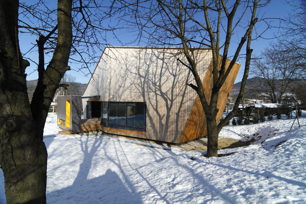 Drevená fasáda domu sa počas slnečných dní stáva premietacím plátnom na ktorom sa násobí okolitá príroda.