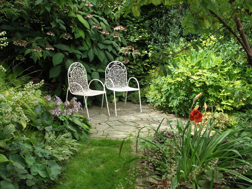 Ak chceme tienisté priestory pod veľkými stromami oživiť, pomôžu nám okrem výsadieb aj malé odpočívadlá. Ideálny je biely záhradný nábytok, ktorý tienistú partiu presvetlí.