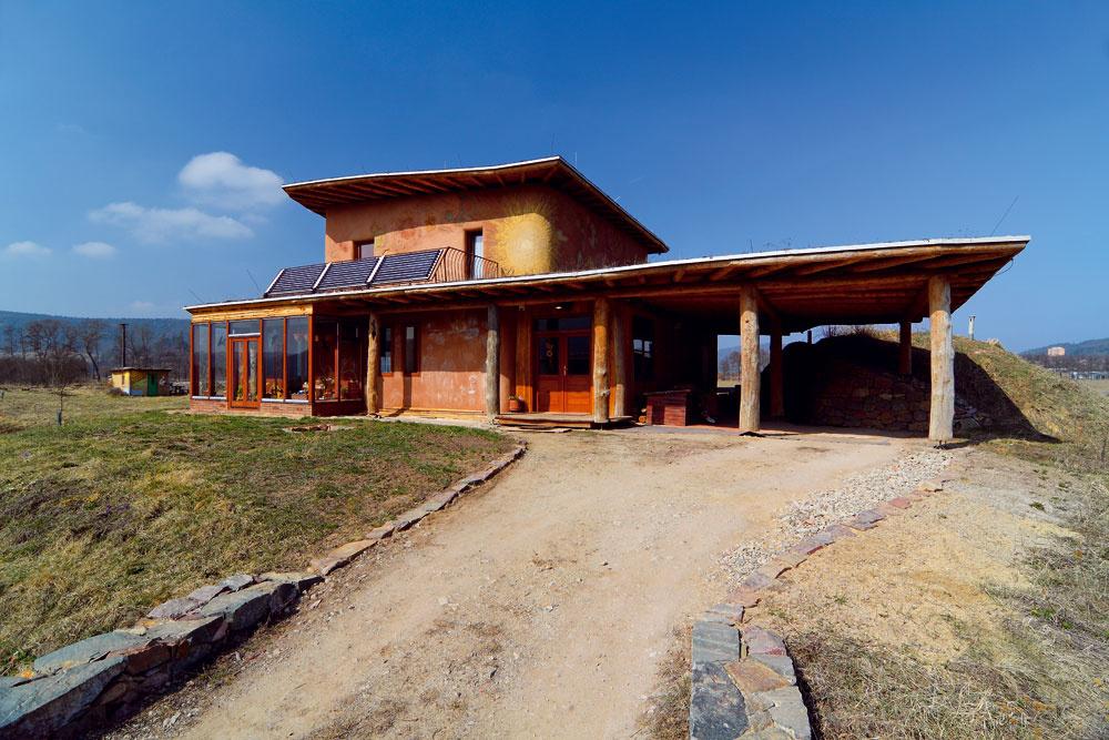 """Celý dom je postavený ztroch výhradne prírodných materiálov pochádzajúcich zbezprostredného okolia – dreva, slamy ahliny. Dokazuje, že aj moderné stavby môžu byť úplne ekologické ablízke prírode. """"Nie je dôvod odopierať si štandard. Môžeme sa však pritom správať zodpovedne,"""" tvrdia jeho obyvatelia."""
