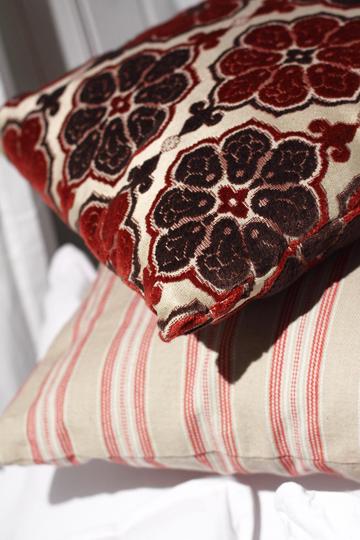Bielo-červený pásikový vankúš, 45 × 65 cm, cena 19,70 €. Vyšívaný vankúš sbordovo-hnedými kvetmi, 45 × 65 cm, cena 29 €. Predáva Elmina, Light Park. www.elmina.sk