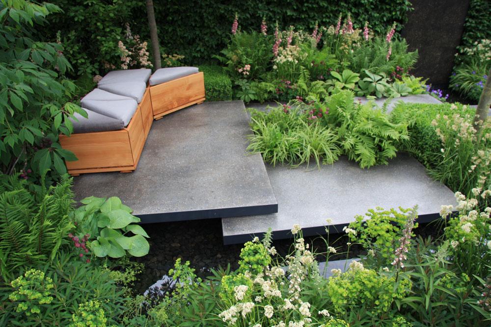 Centrom záhrady je terasa – akési pódium, na ktorom sú umiestnené pohovky. Tie sú zároveň aj praktickým úložným priestorom.