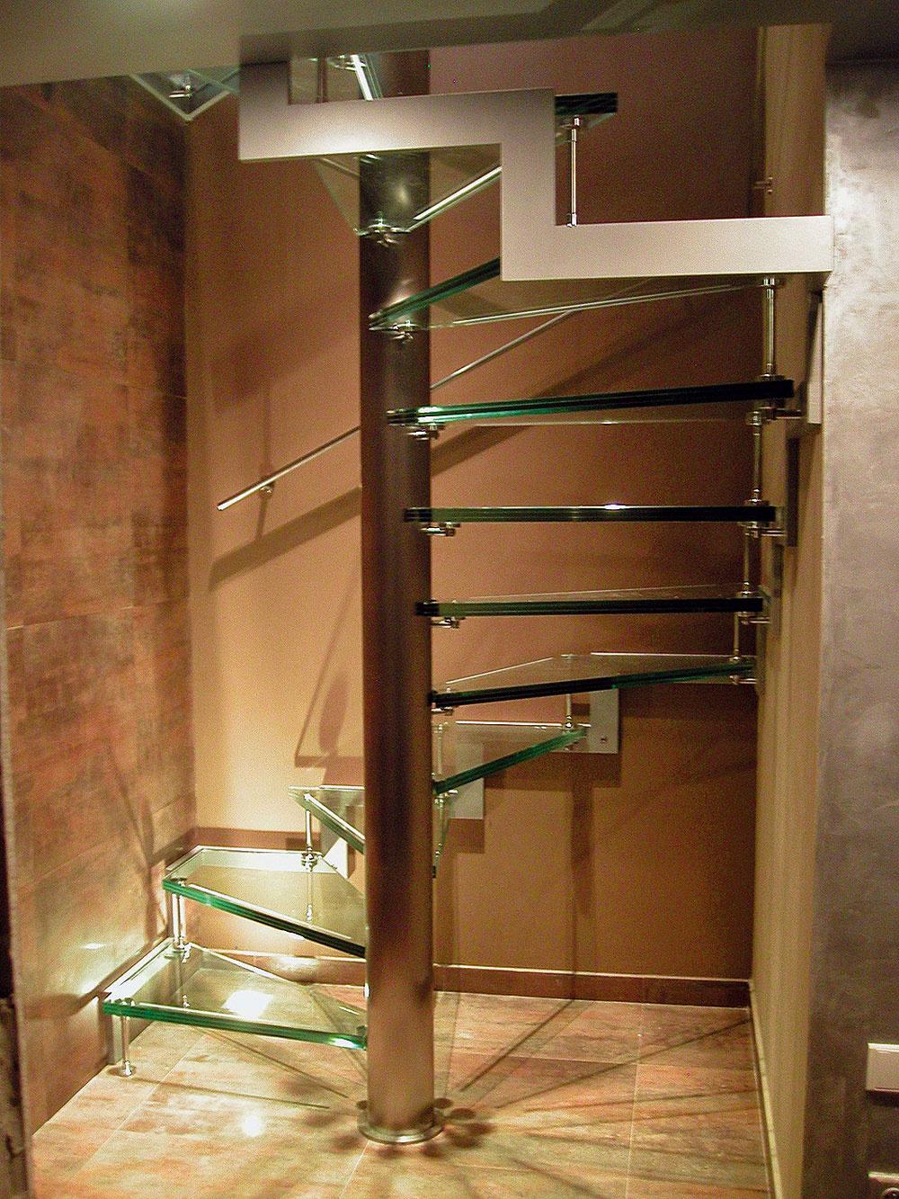 Atypické elegantné vretenové schodisko na štvorcovom pôdoryse. Vreteno avonkajšie schodnice sú zjemne brúseného antikora, nášľapy zvrstveného číreho skla spieskovanými protišmykovými pásikmi. Toto schodisko už nepotrebuje nijaké ďalšie doplnky, samo osebe sa stalo ozdobou interiéru.