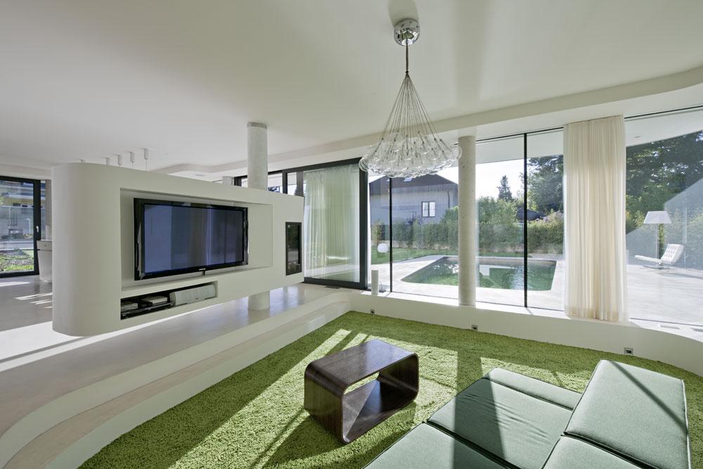 Obývačka akuchyňa sjedálňou tvoria jeden priestorový celok. Len čiastočne ich od seba oddeľuje biely nábytkový prvok – zjednej strany je na ňom umiestnený televízor, zdruhej slúži ako vitrína vjedálni. Nosný prvok nábytku sa využil aj na vedenie komína ku kozubu.