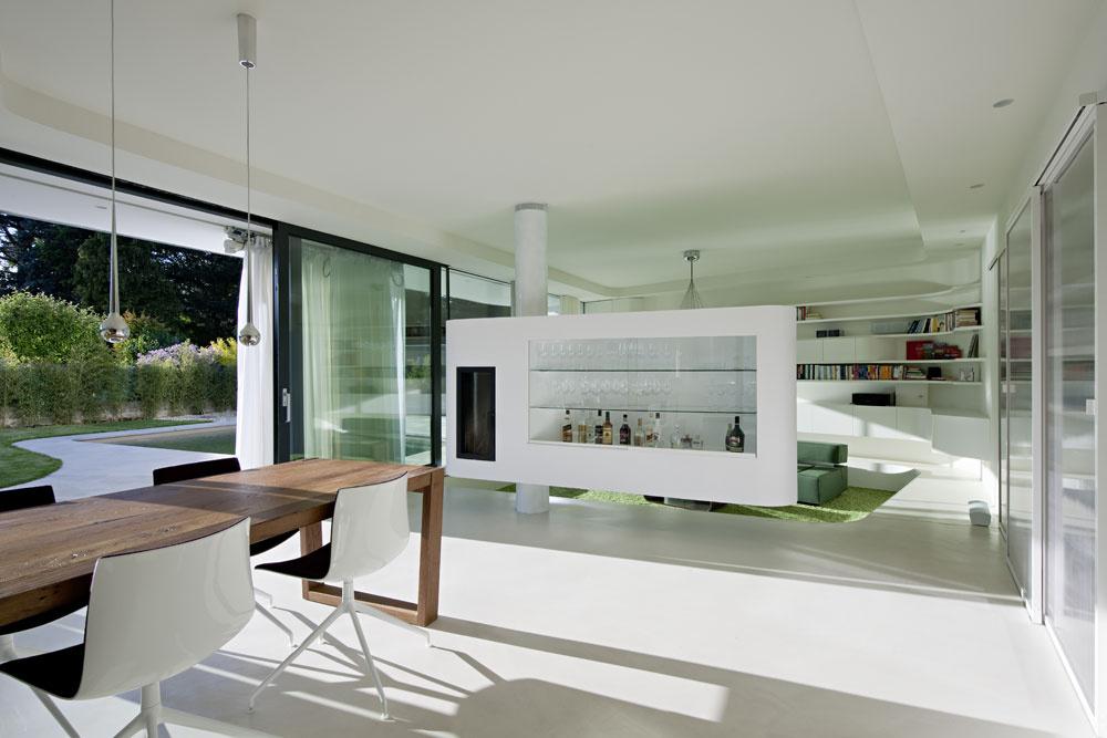 Za sklenenou fasádou prízemia sa nachádza denná časť domu – obývačka akuchyňa sjedálenským stolom. Počas teplých mesiacov sa stávajú súčasťou záhrady alebo naopak. Umožňuje to systém posuvných zasklení, ktoré možno jednoduchým pohybom otvoriť tak, aby nič nestálo vceste pohybu po zjednotenom priestore domu sozáhradou.