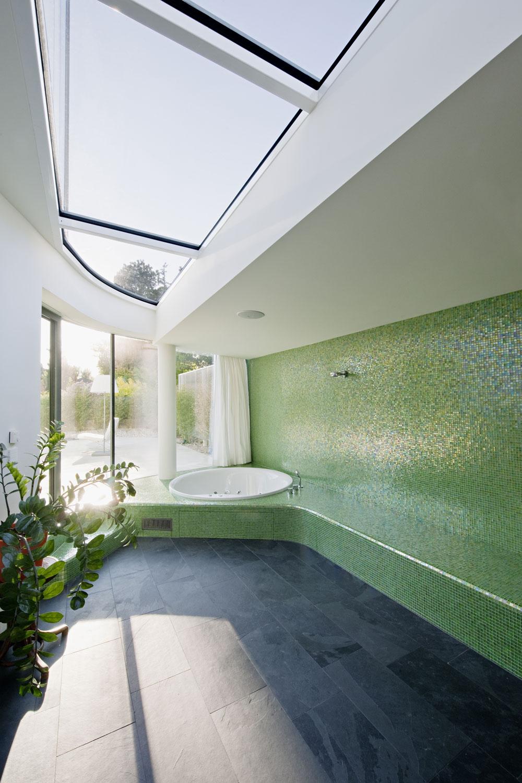 Exkluzívnym výhľadom do záhrady sa môžete kochať aj voveľkoryso koncipovanej kúpeľni. Jej rozmery apoloha ju predurčili stať sa domácim wellnes, obzvlášť počas teplých letných mesiacov, keď sa jej možnosti rozšíria ozáhradný bazén. Vzime poskytuje obyvateľom domu dostatok miesta na oddych afitnes spotrebnou dávkou denného svetla. Mozaikový obklad sľahkosťou kopíruje oblé línie, svetlo arastliny dodávajú priestoru ľahkosť apozitívnu energiu.