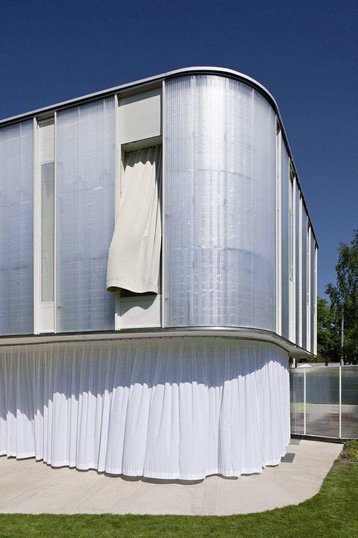 Za horúcich letných popoludní pomáhajú zatieniť obytný interiér biele závesy, namontované pred sklenenou fasádou prízemia. Biela farba odráža slnečné lúče azároveň prepožičiava domu zaujímavý (vz)letný vzhľad.