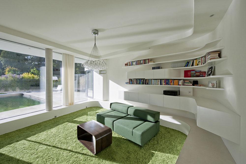 Vinteriéri je všetko navrhnuté ergonomicky adôsledne až do detailov, sdôrazom na oblé línie. Podlaha obývačky je oproti kuchyni znížená, čím sa vytvorí more možností na sedenie aj príjemné miesto na hry sbatoľaťom. Aj tu si možno užiť výhľad do záhrady či vychutnať si pohľad na západ slnka.