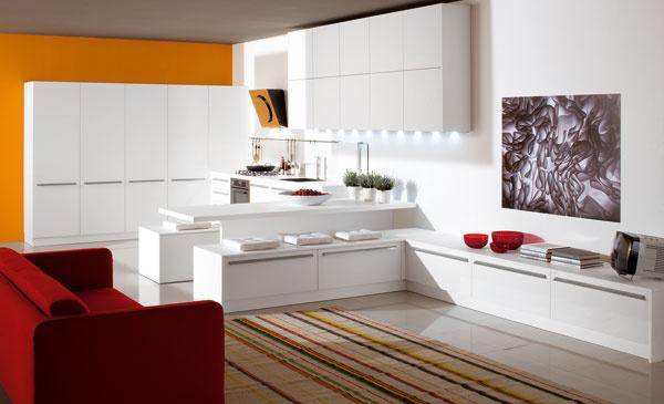Kuchyňa sobývačkou Ethica decorativo od firmy Veneta Cucine zbieleho laminátu. Barový pult opticky delí miestnosť, nízke úložné skrinky plnia aj funkciu sedenia za kuchynským pultom. Rozmery: 304 × 754 cm. Cena na vyžiadanie upredajcu. Predáva Design House.