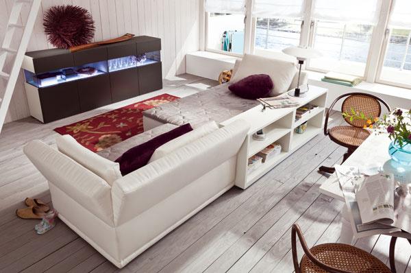 Pohovky Now Home Lounge Madison čalúnené bielym textilom. Rozmery: š 143 × h 104 × v76 cm, cenaod 1660 €. Prídavná skrinka zorechového dreva sbielym lakom. Cena 415€. Vzadu komoda zkolekcie now!15 sosvetlením, šírka 210 cm, cena 1315 € + osvetlenie 527 €. Všetko od firmy Hülsta. Predáva Merito.