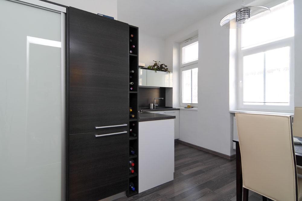 Za rohom, smerom do chodbičky, pokračuje linka vysokými skriňami. Rozšírili sa týmodkladacie priestory vkuchyni – za posuvnými dverami sa skrylo všetko, čo nemusí byť neustále na očiach, vrátane mikrovlnky, je tu miesto na zabudovanú chladničku aj potravinovú skriňu.