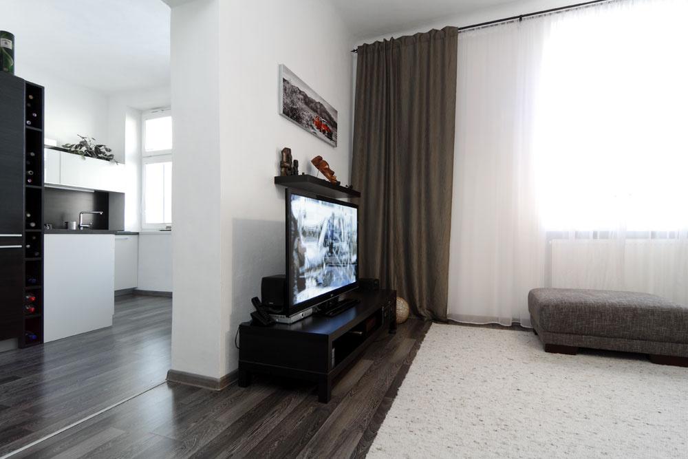 Zkuchyne sa vchádza do obývačky veľkým portálom bez dverí – architektka denné miestnosti včo najväčšej možnej miere prepojila, aby sa podporil dojem priestrannosti aotvorenosti. Pocit jednoliateho priestoru umocňuje aj laminátová podlaha, ktorá je jednotná vcelom byte okrem kúpeľne.