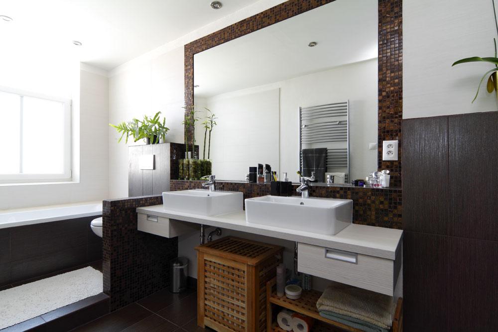 """Keďže kúpeľňa bola pomerne dlhá, jedno umývadlo by tu vyzeralo smiešne,"""" vysvetľuje Katarína. """"To, že dve sú nakoniec aj praktickejším riešením, ocenil časom aj domáci pán,"""" usmeje sa. Úlohou veľkého zrkadla je priestor opticky rozšíriť."""