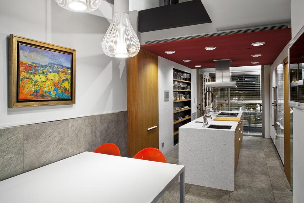 Na oboch stranách svetlíka sa otvárajú atraktívne priestory vodvojnásobnej výške, ktoré pomáhajú opticky tlmiť extrémnu dĺžku domu: nad raňajkovou jedálňou je priestor oveľa dlhší ako na opačnej strane vobývačke. Zariadenie aspotrebiče sú od popredných firiem Pedini aGaggenau. Ďalšiu príležitosť na stolovanie na polykarbonátových stoličkách Louis Ghost od Philippa Starcka (Kartell) ponúka vkuchyni hlboká lodžia, ktorá je skrytá za lamelami.