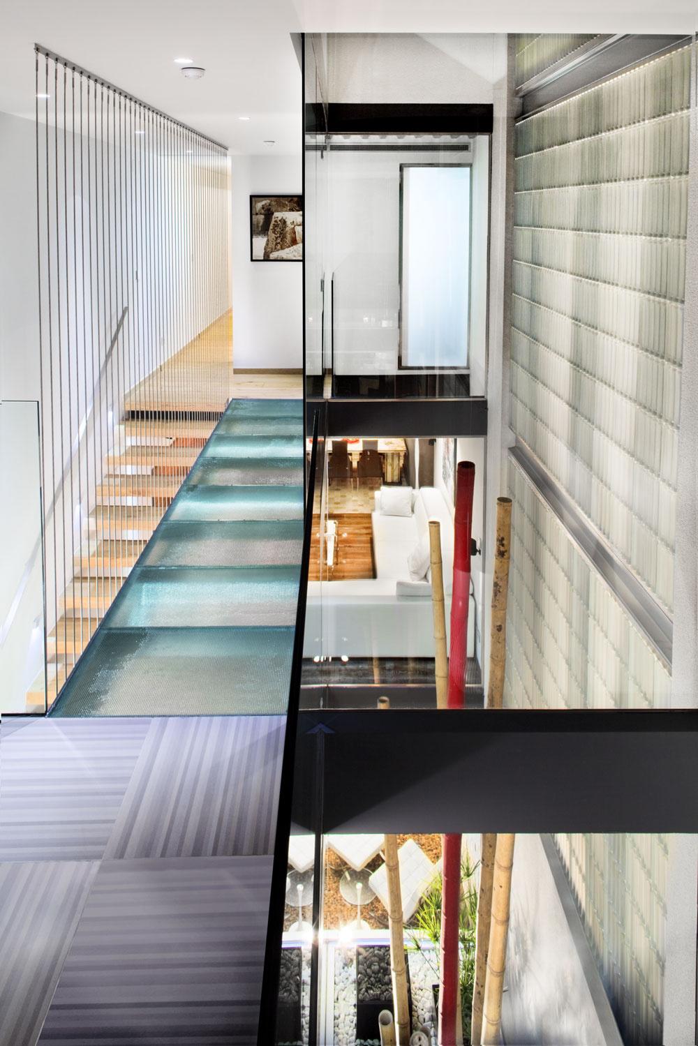 """""""Premostenie"""" zvrúbkovaného skla medzi priestorom pre malé deti arodičovským apartmánom, ktorý sa sem obracia oknom do sprchy. Vzhľadom na ráz domu vyhovovalo architektovi spájať rovnaké prvky vertikálnym smerom, nie horizontálnym – plocha svetlého dreva podlahy rodičovského apartmánu sa spája snášľapnými doskami schodiska adetailmi zariadenia kuchyne talianskeho výrobcu."""