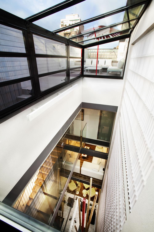 Vtomto pohľade cez svetlík kbazénu, ktorý sa naskytne od točitého schodiska, dobre vidieť profil sklenených dielcov, pripomínajúci kanelúru klasických stĺpov – pomenovali ich Doric Bloc. Vpohľadoch ztejto strany vytvára pomyselnú vertikálu biely nábytok, ktorý sa uplatňuje na jednotlivých podlažiach.