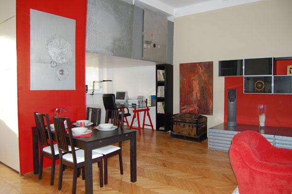 Obývacia izba alebo 4 v1 Pri zachovaní všetkých funkcií sme priestor farebne zjednotili avýrazne odčlenili jednotlivé zóny. Všetko má svoje miesto – aj nový jedálenský stôl so stoličkami amoderný písací stôl, ktorý sa zapojil do červenej tóniny miestnosti.