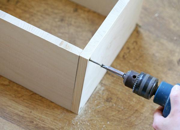 Dosky si uložte do požadovaného tvaru police (môžete jednou stranou oprieť ostenu) azbočnej strany navŕtajte do každého rohu (asi 1cm od krajov) diery zodpovedajúce veľkosti samorezných skrutiek. Skrutkypritiahnite pomocou vŕtačky alebo ručne.