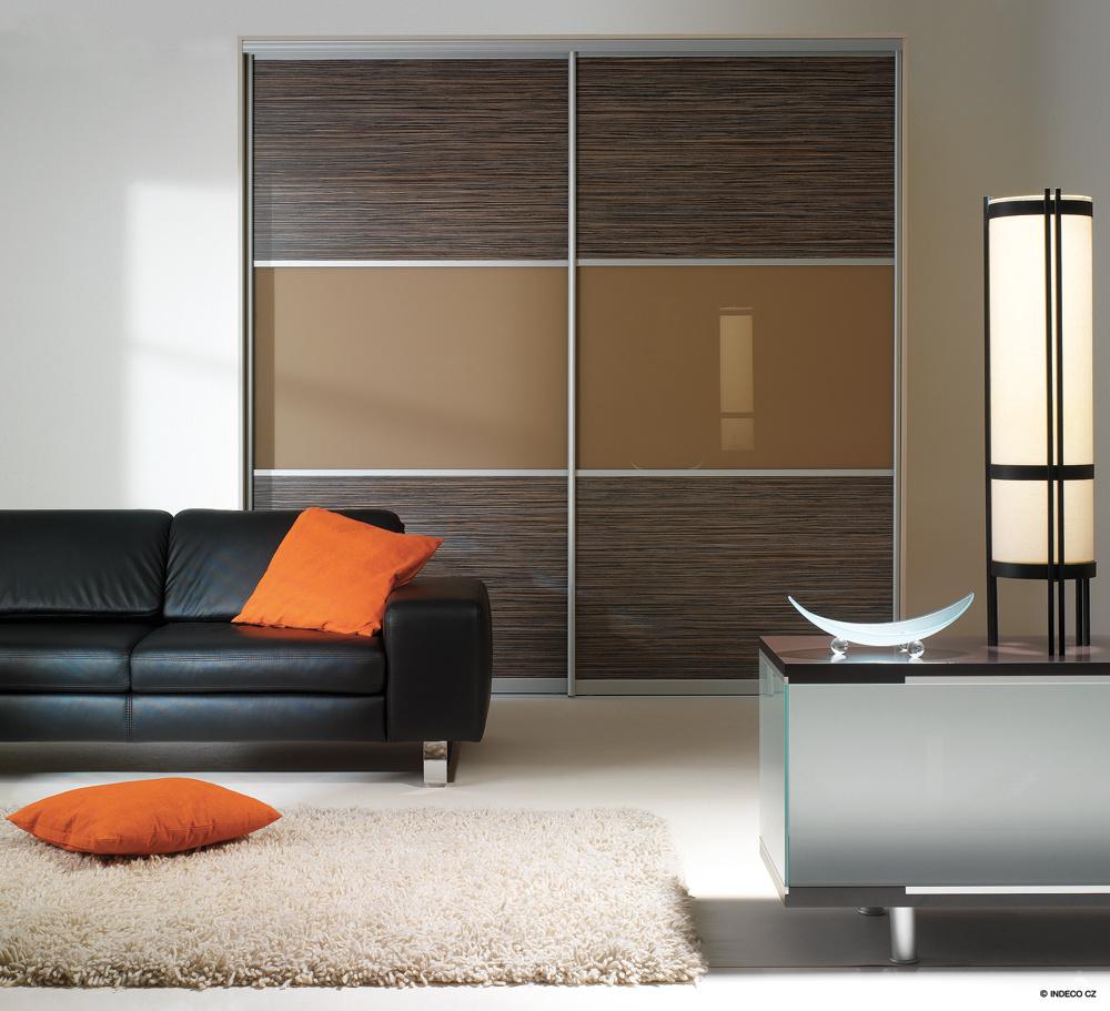 Horizontálne členenie výplne posuvných dverí vstavanú skriňu uzemňuje a dáva jej monumentálny výraz. V návrhu sa strieda drevodekor s lacobelom v smere, ktorý celý interiér upokojuje. Aj napriek doplnkom s výraznou červenou  farebnosťou pôsobí priestor stabilizujúcim dojmom.