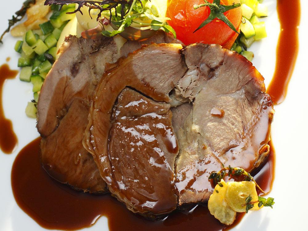 hlavné jedlo  Pečené jahňacie stehno scuketou amajoránom na zemiakovom pyré   1,2 kg vykosteného jahňacieho stehna  1 dcl olivového oleja 2 mrkvy 2 petržleny 1 zeler 2 cibule 6 strúčikov cesnaku 1 kg zemiakov 150 g masla 2 cukety mlieko čerstvý majorán vetvička rozmarínu atymianu soľ, korenie   Pracovný postup 1.Na pekáč poukladajte nakrájanú koreňovú zeleninu, cibuľu, nasolené mäso, rozmarín,tymian acesnak. Podlejte vodou aolejom. Pečte vrúre asi 1,5 hodiny na 170 °C. 2.Zuvarených zemiakov, masla amlieka urobte hladké pyré.  3.Cuketu si nakrájajte na malé kocky aopražte na olivovom oleji, dochuťte soľou ačerstvým majoránom. 4.Na tanier servírujte zemiakové pyré scuketou, na pyré položte plátky upečeného jahňaťa apolejte šťavou.  Mäso počas pečenia otáčajte apodlievajte vypečenou šťavou. Po upečení ju zlejte, povarte apolejte ňou mäso pri servírovaní.  Zemiakové pyré môžete ochutiť olivovým olejom.