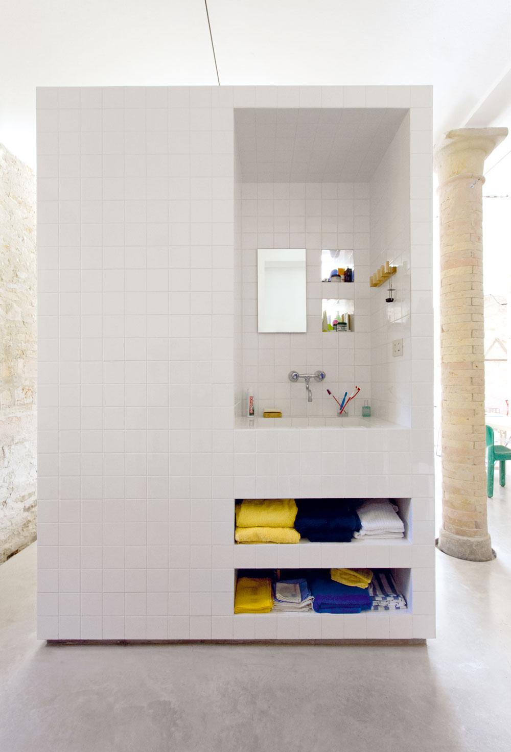 Kúpeľňu tvorí len masívny biely blok, voľne stojaci na betónovej podlahe.