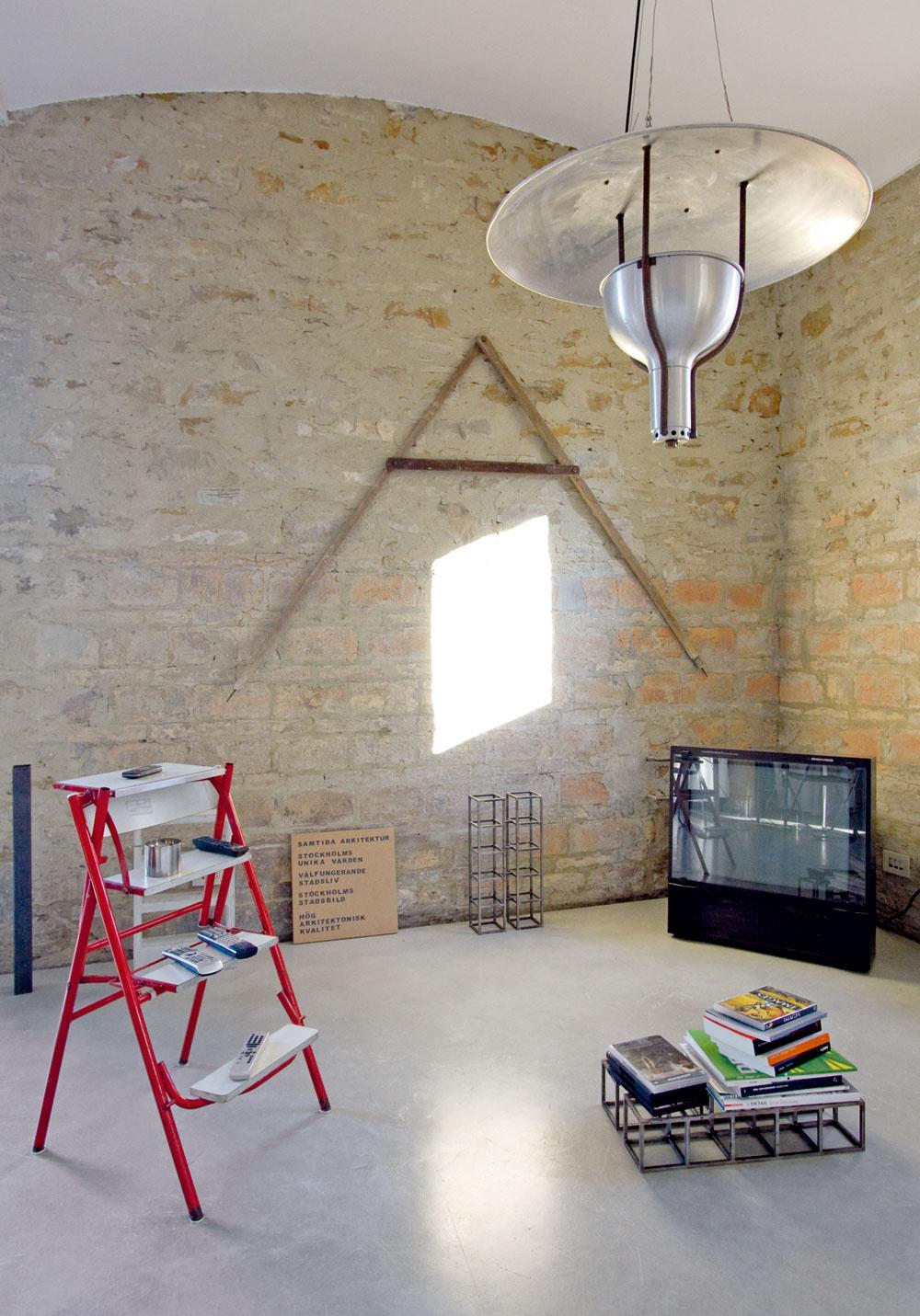 Obývací kút je vybavený dočasnými doplnkami – maliarskymi schodíkmi, ktoré slúžia ako poličky, či kovovými štruktúrami použitými namiesto konferenčného stolíka.