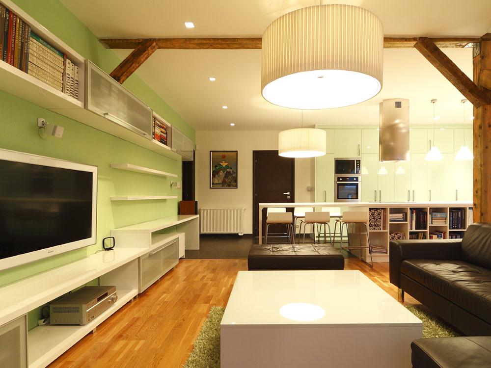 Vďaka rôznym svietidlám je večer vbyte úžasná atmosféra – bodové osvetľujú steny, výrazné závesné lampy zas vymedzujú priestor kuchyne, jedálne aobývačky. Takéto množstvo náladových svetiel umožňuje vytvoriť rôzne svetelné scény, ktoré vždy inak vymodelujú podkrovný priestor. Najmä teplé žlté svetlo veľkých lámp pôsobí veľmi efektne avytvorí podobnú útulnú atmosféru ako oheň zkozuba.