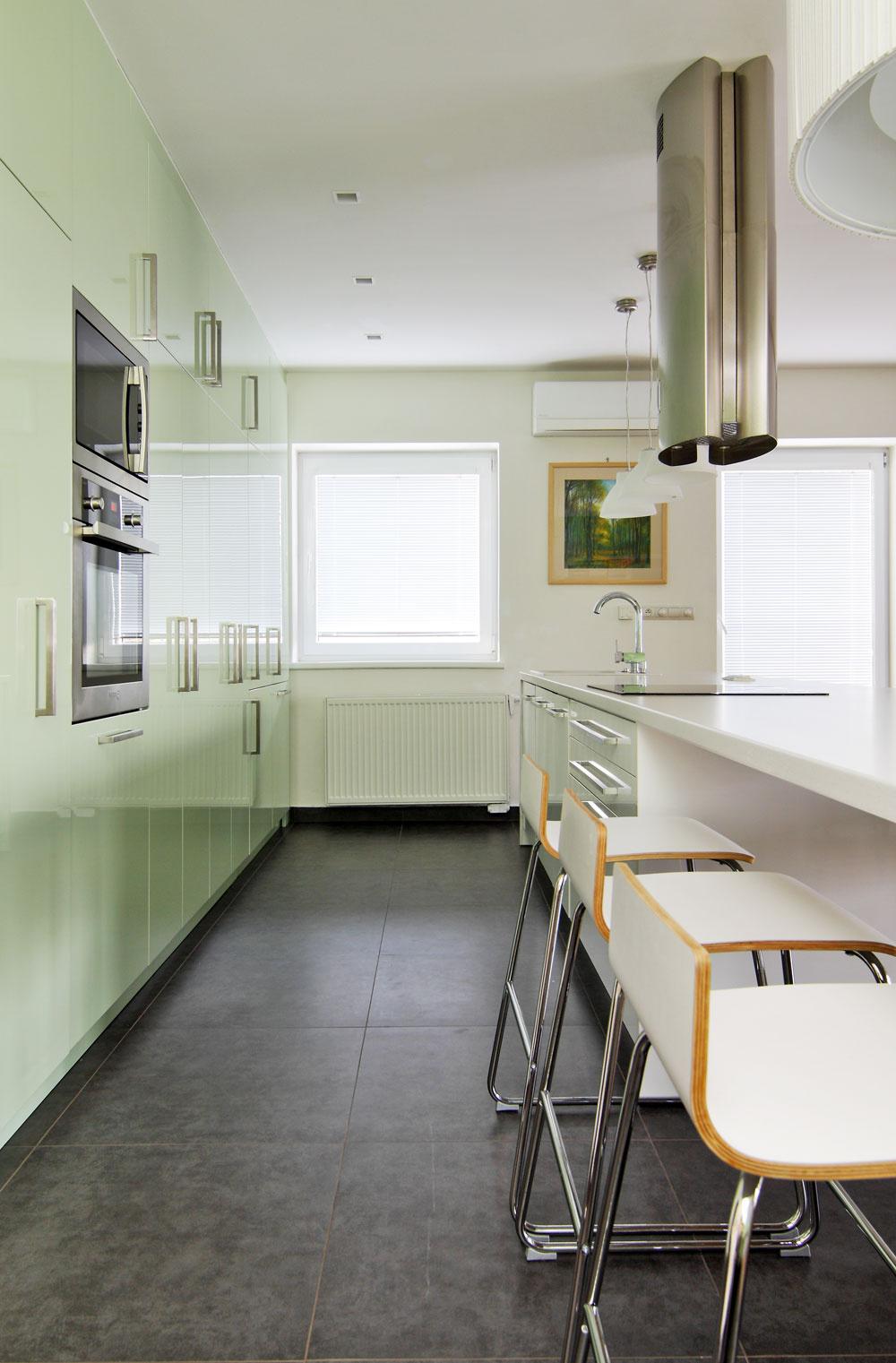 Na základe projektu od architekta sa realizácie interiéru chopili jeho budúci obyvatelia sami. Domáca pani vybrala aj dominantnú pastelovozelenú farbu, ktorá sa prejavila najmä na obývačkovej stene avysokých skrinkách kuchynskej linky. Zelená je totiž jej obľúbená. Na mieru vyrobená kuchynská zostava skryla aj komínové prieduchy – vtej časti museli byť skrinky plytšie.