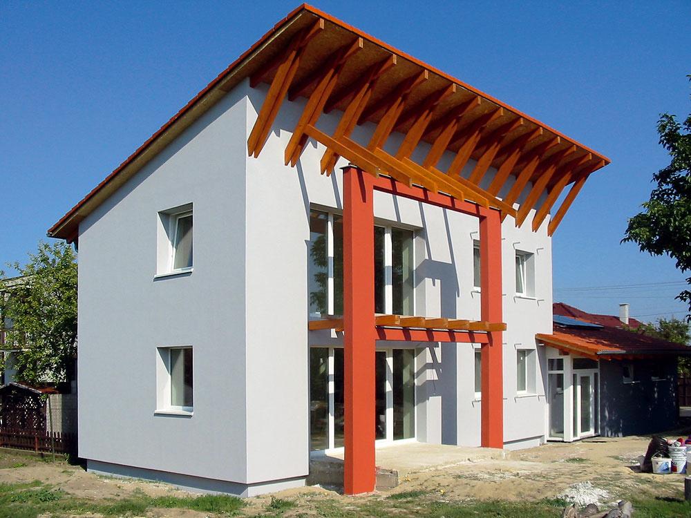 Na konštrukciu stropov aobvodových stien pasívneho rodinný dom vPustých Úľanoch sa použil systém od firmy Wienerberger. Obvodové steny sú zo systému POROTHERM 38 Profi, ktorý je založený na murovaní zpresných tehlových blokov, čo zlepšuje tepelnoizolačné vlastnosti steny ajej neprievzdušnosť. Masívny keramický materiál má zároveň aj výbornú akumulačnú schopnosť. Teplo, ktoré prijme vpodobe zimných pasívnych solárnych ziskov, postupne uvoľňuje do interiéru. Na dosiahnutie parametrov pasívneho domu bolo potrebné steny ešte doizolovať minerálnou vlnou vhrúbke 250 mm. Táto izolácia sa použila aj vpodlahách nastyku sterénom avstreche (350 mm). Vylúčenie tepelných mostov je zabezpečené šikovným konštrukčným návrhom jednotlivých rizikových detailov. Dom bol dokončený vroku 2010.