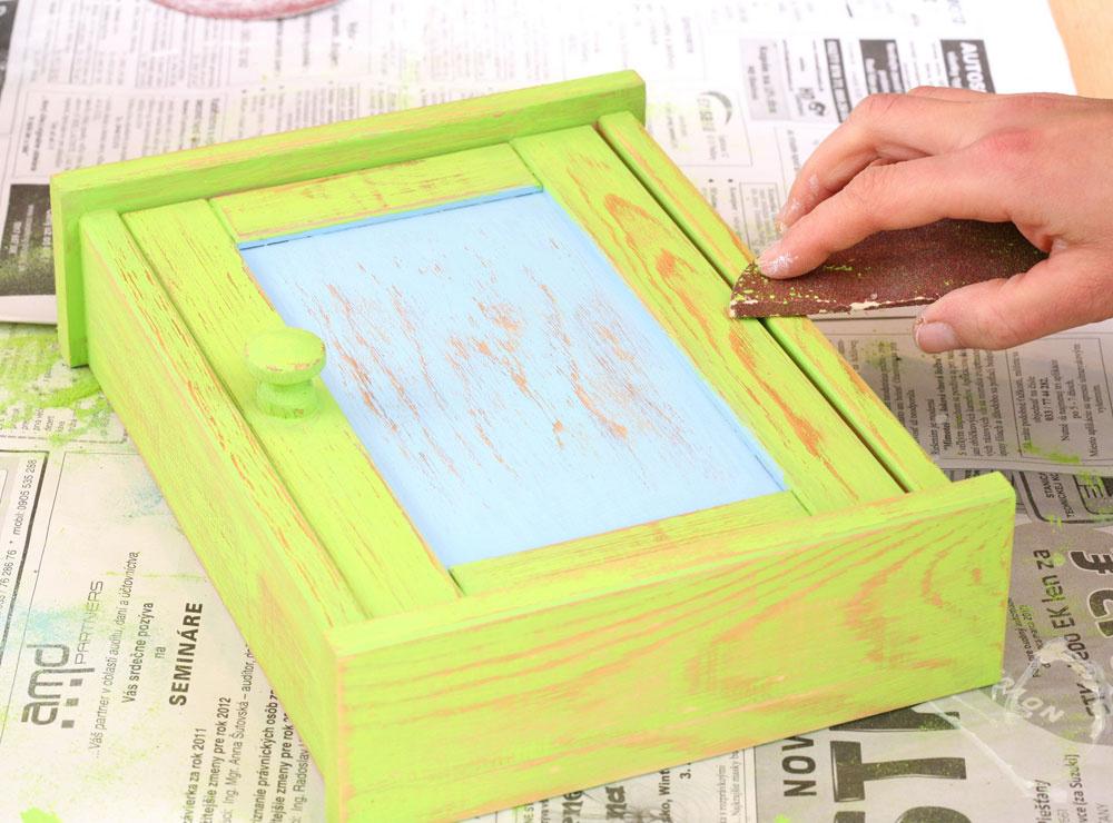 4. Keď farba na skrinke uschne, jemne ju prebrúste brúsnym papierom – tak získa štruktúru dreva apatinovaný vzhľad.