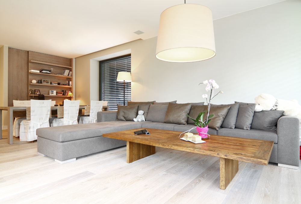Zariadenie vminimalistickom štýle afarebných odtieňoch sivej dopĺňa aoživuje vobývacej izbe dubový konferenčný stolík so vzhľadom recyklovaného dreva.