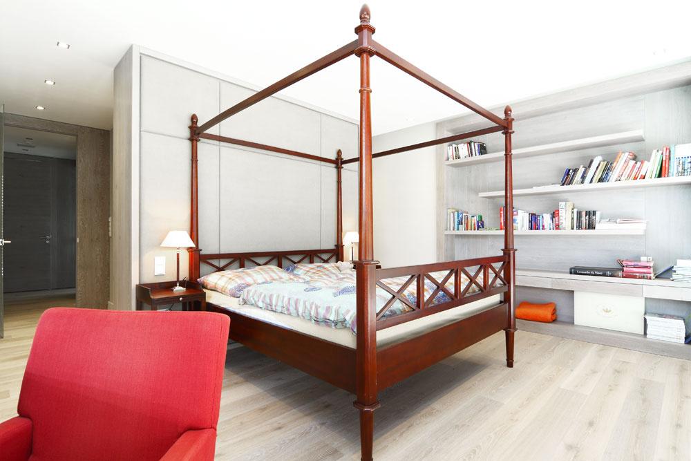 Trocha hravosti vnáša do minimalistického interiéru vodtieňoch sivej drevená posteľ anočné stolíky sozdobnými prvkami, ale aj červené kresielko pri toaletnom stolíku.