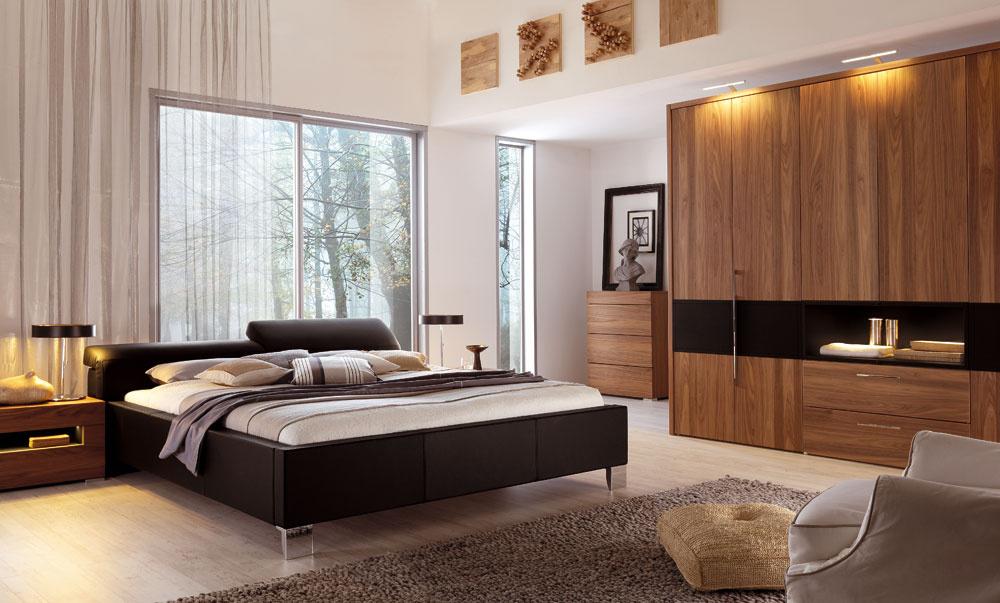 Posteľ Elumo IIod firmy Hülsta svýškovo nastaviteľným čelom zkože (čierna, biela, piesková, nugátová alebo drevo sbielym matným lakom, orechová dyha). Rozmery: 160/180/200 × 200 cm. Cena 5 439 €.