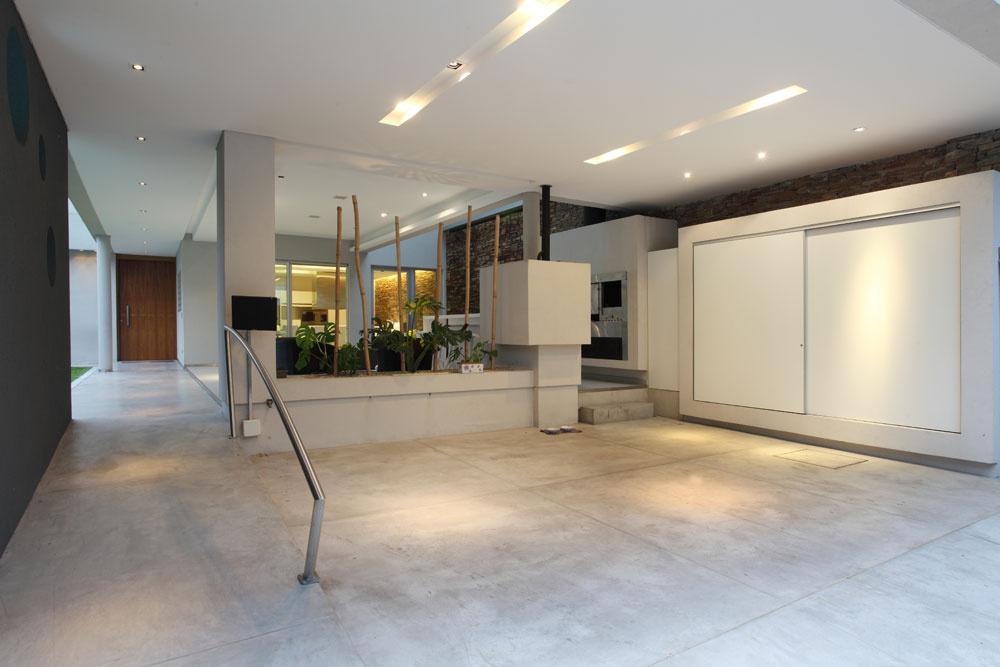 Vkrytom priestore na parkovanie členia podlahu zlešteného betónu ryhy, aby ladila sveľkoformátovou dlažbou vexteriérovom obytnom priestore, takzvanej galeríi. Približne pätnásť metrov dlhý priestor od brány ku kuchyni pomohla skrátiť kompozícia zhranolov. Je vnich miesto na odkladanie agril.