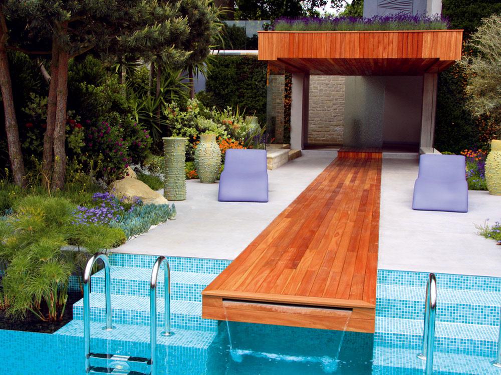 Betónovú terasu sdreveným kobercom spestrujú plastové ležadlá aumelecké vázy od Davida Shilinga. Ostrapatosť strechy sa postarala výsadba levandúľ.