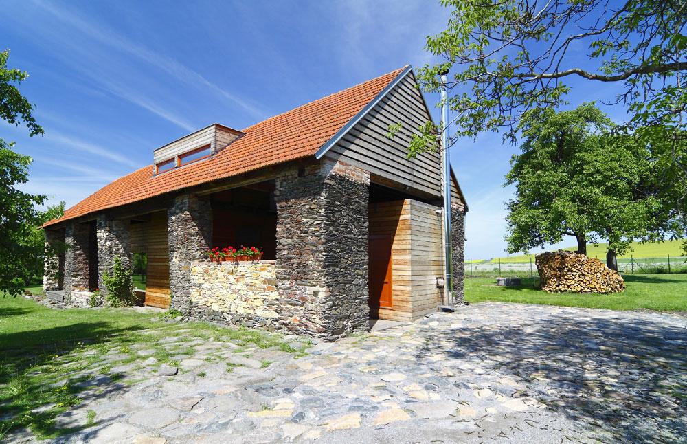 Nový drevodom postavený vstarej kamennej stodole je spojením minulosti so súčasnosťou. Staré kamenné múry do určitej miery chránia novostavbu arobia dom iným anezabudnuteľným.