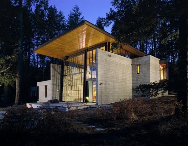 Masívne okno o rozmeroch 9 x 6 m otvára priestor a haromonicky prepája interiér s prostredím neďalekého lesa a jazera.