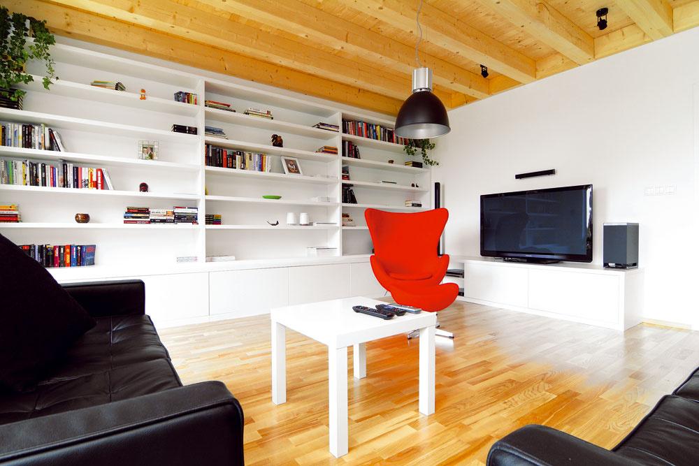 Červené kusy nábytku, ako napríklad kreslo na motívy dizajnu Egg chair, vytvárajú kontrast kstrohej čiernej sedacej súprave (podľa sedačky Florence Knoll Sofa od Eliela Saarinena) anenápadnému bielemu nábytku.