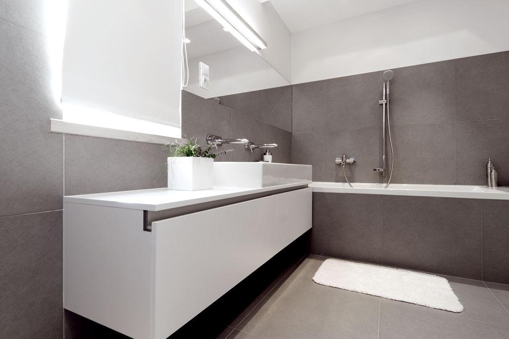 """Taktiež do kúpeľne na poschodí sa prenáša myšlienka praktického využitia priestoru. Šikovne je vyriešený odkladací priestor pod umývadlom – vpodobe priestranných zásuviek. Vkúpeľni je obklad len na nevyhnutnej ploche, aby pôsobila """"civilnejšie"""". Na neobkladaných častiach steny je  biela štruktúrovaná tapeta odolná proti vode."""